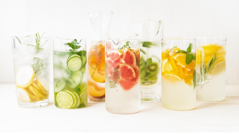Trockene Mundschleimhaut: Sieben Gläser sind gefüllt mit Wasser. Jedes Glas ist zusätzlich mit verschiedenen Früchten und Kräutern gefüllt.