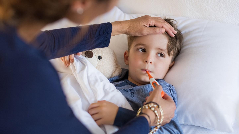 Durchfall und Fieber: Kleiner Junge liegt mit Teddy im Bett, ein Fieberthermometer im Mund. Eine Frau legt die Hand auf seine Stirn.